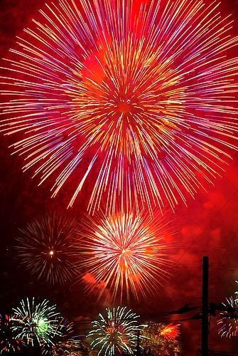Photograph of a red sky filled with fireworks.