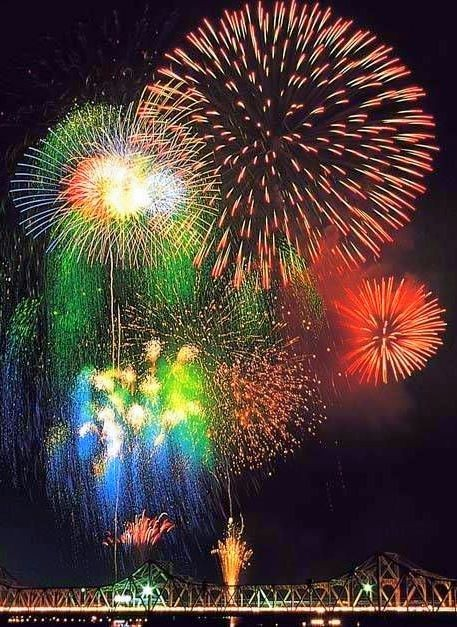 Photograph of colorful fireworks over a bridge.