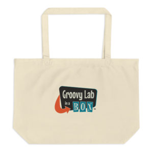 Photograph of a cream colored tote bag with the Groovy Lab in a Box logo.
