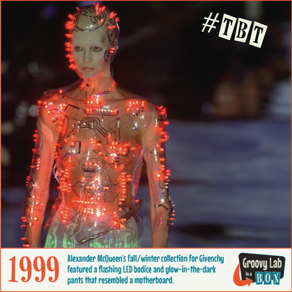 Photograph of a model wearing a clear bodice covered with LED lights that resemble a circuit board.  The circuit board and LED lights also go around the models head.